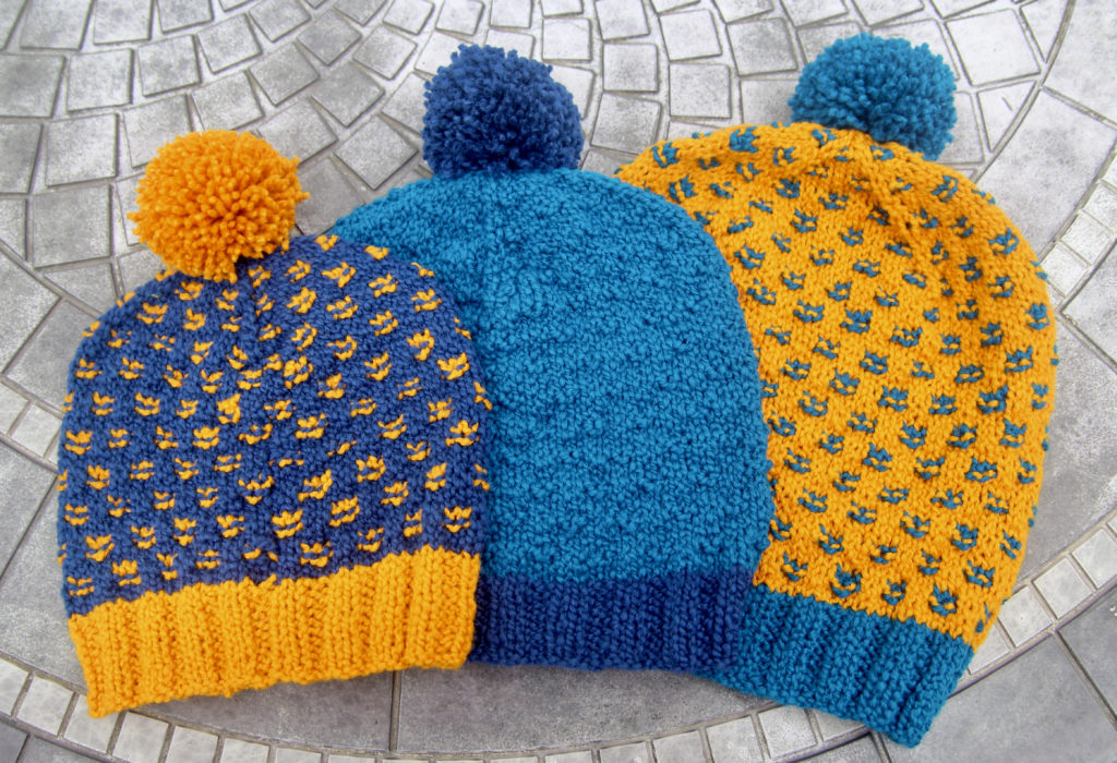 Three handknit hats sizes small to large, in shades of navy, turquoise and bright yellow, lay on a ceramic table.