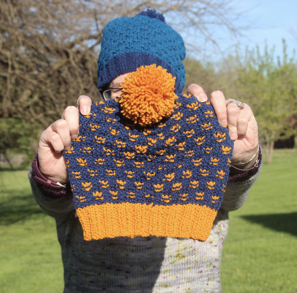A woman wearing a blue hat stands in her garden, hold a small handknit hat in navy with bright yellow brim, accent stitches and a pompom.
