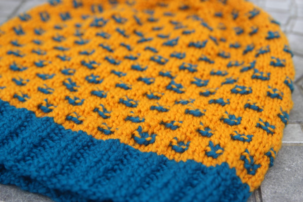 A closeup of a handknit hat, in sunny yellow yarn, with a turquoise brim and  occasional purl stitches.